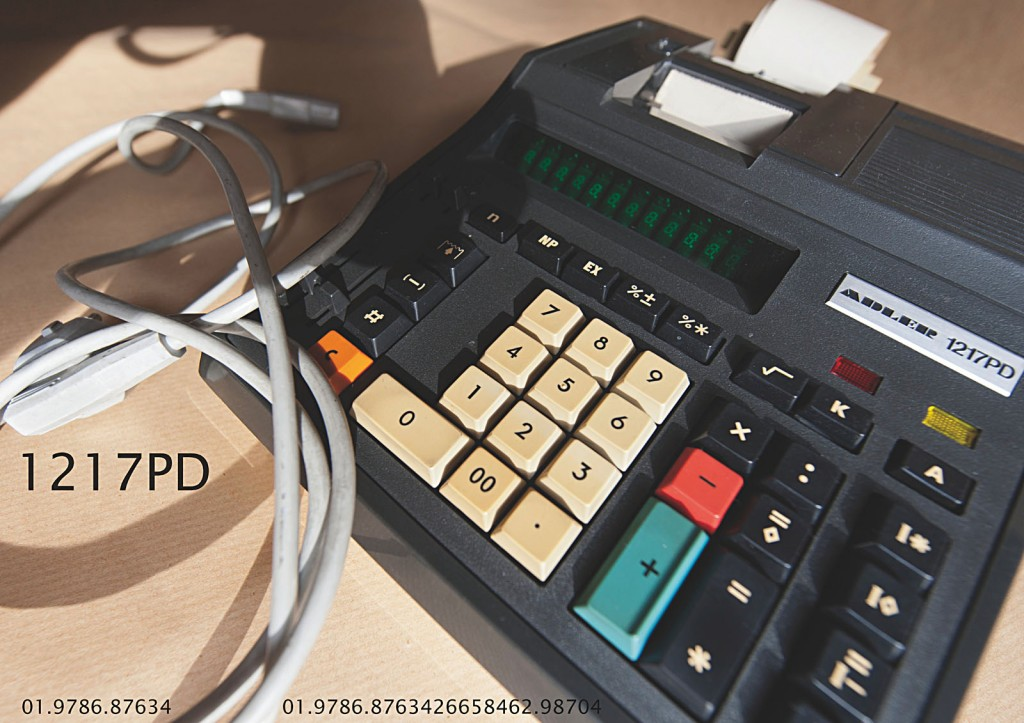 Vierundzwanzig digitale Farbtafeln. Hoch aufgelöst über einen PC auf einem 4K-Display abgespielt. Tafel 3: Unverpackte Rechenmaschine mit Stromkabel seitlich von vorne aufgenommen. Typnummer, elfstellige Projekt- und vierundzwanzigstellige Objektnummer in die Tafel integriert.