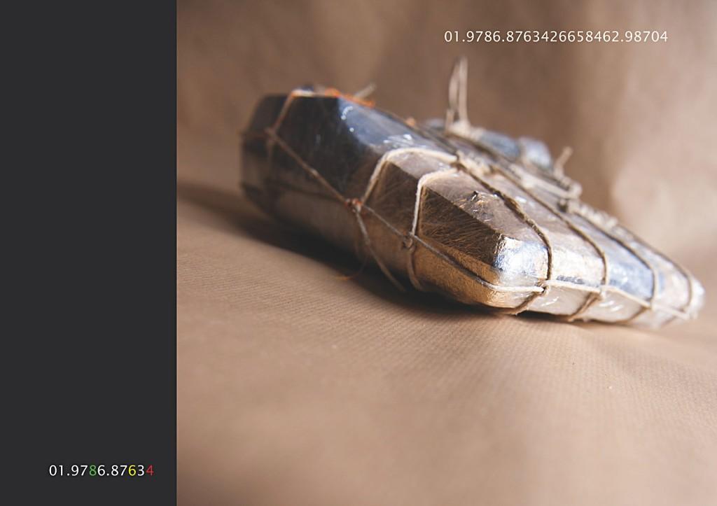 Vierundzwanzig digitale Farbtafeln. Hoch aufgelöst über einen PC auf einem 4K-Display abgespielt. Tafel 16: Marcellus M. Menke: Verpackte Rechenmaschine. Rechenmaschine, Plastikfolie, Kordel, Knopflochgarn, Kompositionsgold, braunes Packpapier, Köln 2012. Hommage à: Christo (Christo Javacheff) Wrapped Calculation Machine, 1963. Linke vordere Seite, schräg von unten aufgenommen. Abdeckung eines Bildteiles durch ein schwarzes Rechteck. Elfstellige Projekt- und vierundzwanzigstellige Objektnummer im Bild in die Tafel integriert.