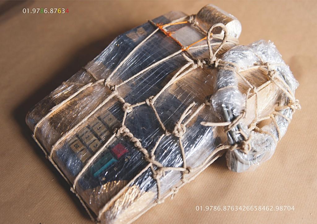 Vierundzwanzig digitale Farbtafeln. Hoch aufgelöst über einen PC auf einem 4K-Display abgespielt. Tafel 19: Marcellus M. Menke: Verpackte Rechenmaschine. Rechenmaschine, Plastikfolie, Kordel, Knopflochgarn, Kompositionsgold, braunes Packpapier, Köln 2012. Hommage à: Christo (Christo Javacheff) Wrapped Calculation Machine, 1963. Um fünfundvierzig Grad geneigte seitliche Draufsicht. Elfstellige Projekt- und vierundzwanzigstellige Objektnummer in die Tafel integriert.