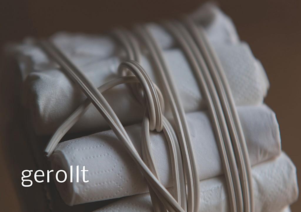 Marcellus M. Menke, Verpacktes Einmachglas, Einmachglas 1/4 l mit gummiertem Weißmetallschraubdeckel, zu Tampons grollte Servietten, Filz, zweiadriges Stromkabel. Signatur auf der Tamponierung. Köln 2013. Tafel 9 von 14 hochaufgelösten digitalen Farbtafeln, 4K-Display, auf Wand montiert, von PC bespielt.